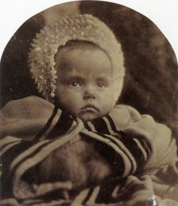 Black and white photograph of a baby in a bonnet.